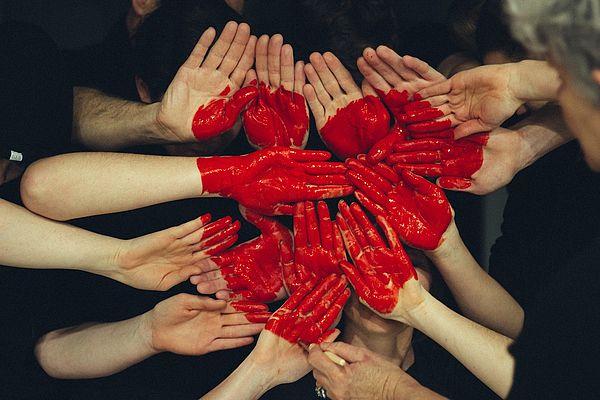 Mehrere teils rot bemalte Hände bilden ein Herz